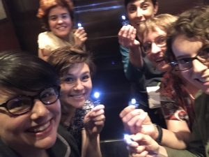 Six women in a semi-darkened elevator, holding their soldered flashlight projects