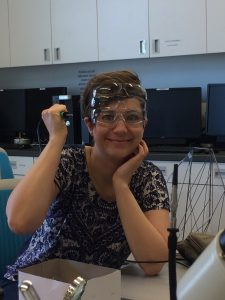 Woman wearing three pairs of safety glasses and holding a soldering iron incorrectly