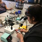 A white woman, seated, looking through magnifying lenses at the circuit she is soldering