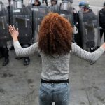 a black woman stands in the foreground, back to the camera and hands up. She faces a line of police officers in riot gear