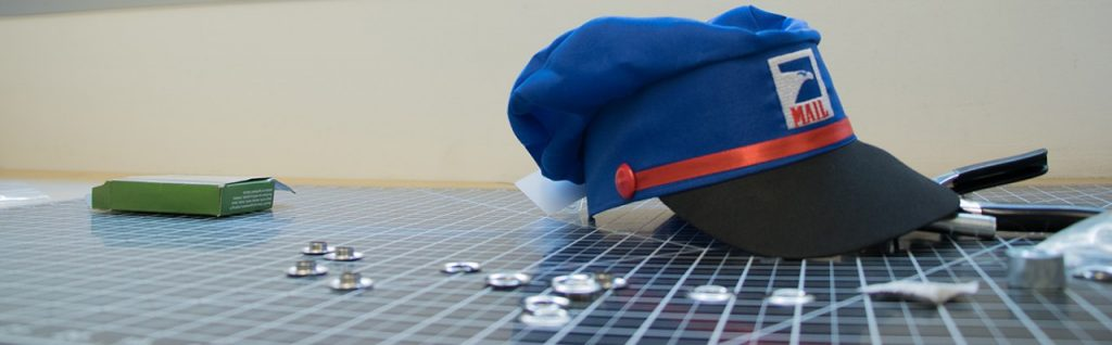 Pretend mail carrier hat sitting on a cutting mat, surrounded by grommets